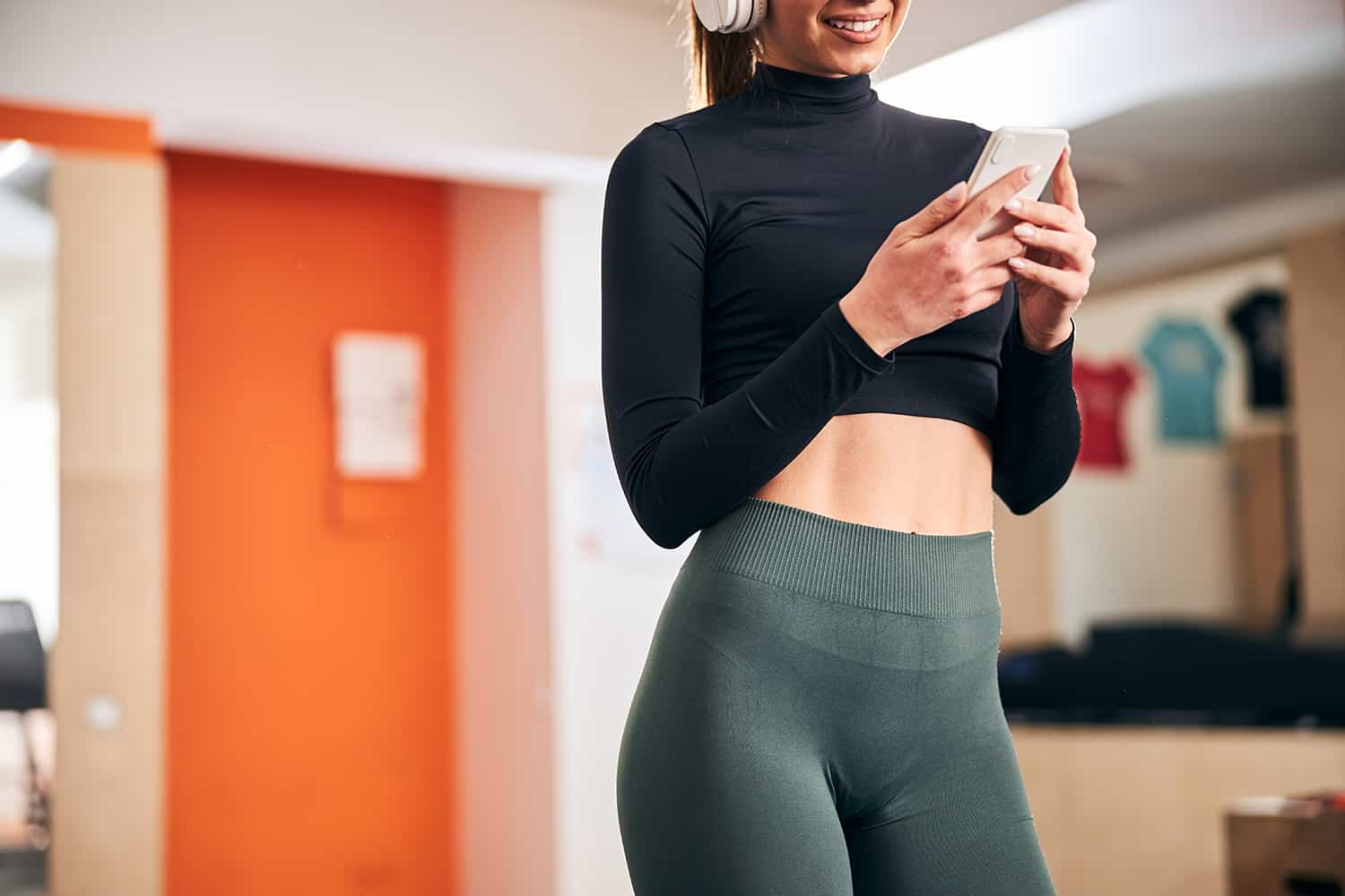 slender young woman checking phone at the gym z7t5bul